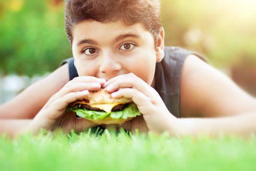 Teen boy eating burger