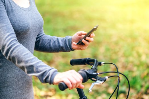 Woman texting and holding bicycle in park