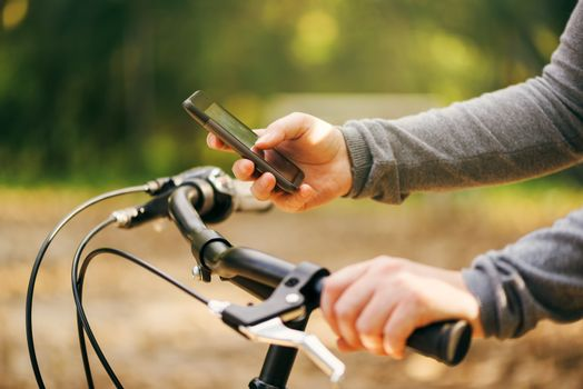 Woman typing text message during bicycle ride