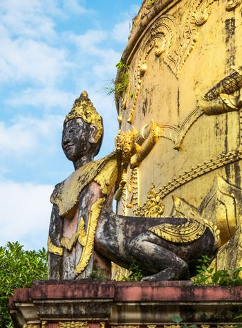 Detail of old pagoda at the Moe Hnying Monastery in Yangon, Myanmar. Sculpture of hybrid creature with human head and animal body in the foreground.