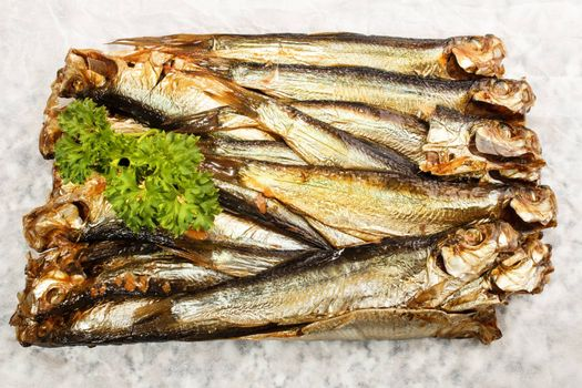 smoked sprats and parsley on white paper
