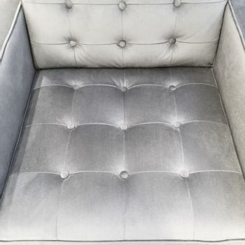 Silky fashionable armchair with decorative buttons