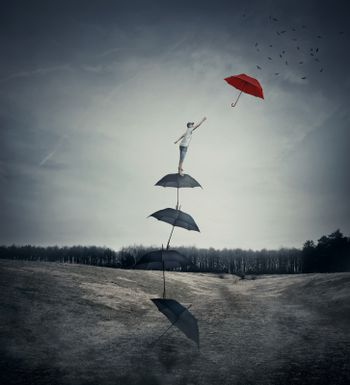 Young boy stand on a stack of umbrellas arranged as a ladder to the sky, trying to catch a different red umbrella. The pursuit of happiness and success concept.
