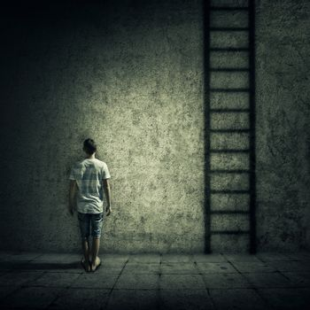Abstract idea with a person standing in a dark room, in front of a concrete wall, figuring a ladder to escape. Surrounded by limitations, daily routine.