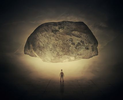 Surrealistic image as a man, with a bag in his back, stand in a foggy street below a huge squeezing rock. Life pressure and stress concept.