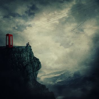 Surreal view as a sad, young man, standing on the edge of a cliff near a red telephone box, waiting someone to call him.