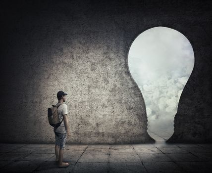 Conceptual image with a person standing in a dark room, in front of a bulb shaped doorway. Escape opportunity, entrance to another world.