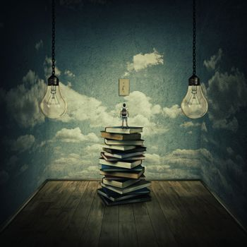 Idea concept with a boy standing on a pile of books trying to swich on the light bulbs, surrounded by concrete walls with clouds texture as thinking limitations. In search of knowlegde.
