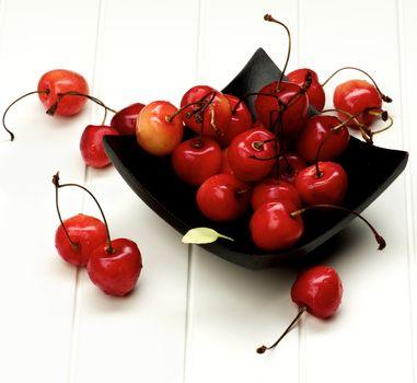 Arrangement of Sweet Maraschino Cherries in Black Wooden Plate closeup on White Plank background