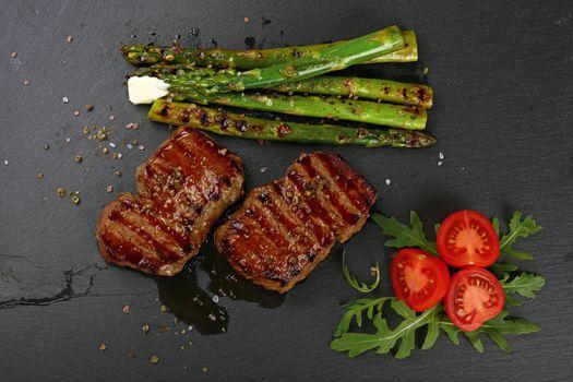 Two grilled beefsteak on black slate board