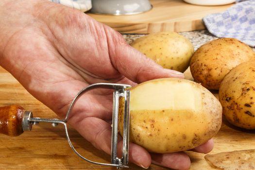 female chef is peeling potatoes