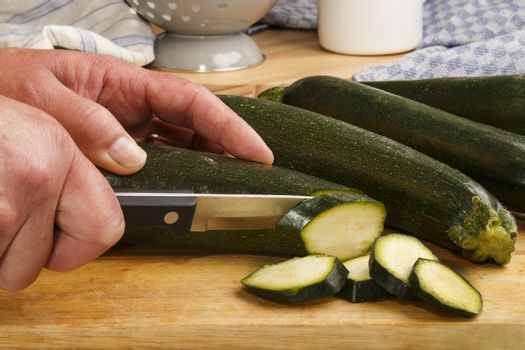 female cuts courgette on wooden board in slices