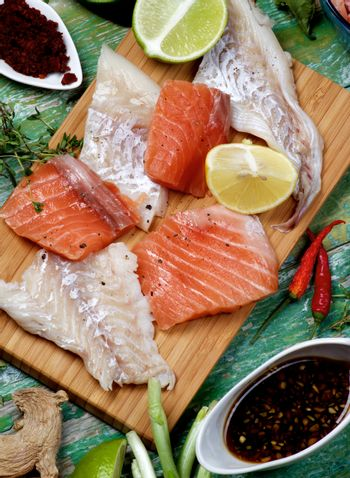 Arrangement of Raw Fillet of Salmon and Cod, Greens, Spices, Sauces and Lemon closeup on Cracked Wooden background