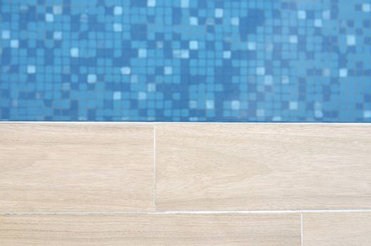 Close focus of edge of artificial wood floor near swimming pool with moving blue water