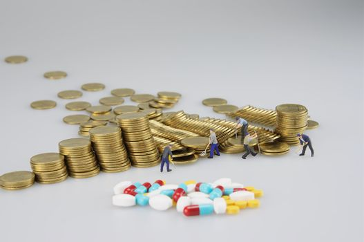 Stack of gold coin with miniature people and medicine on white background.