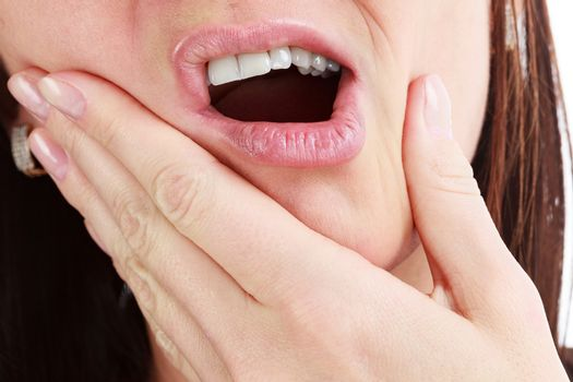 Closeup of woman in strong toothache pain with hands over face. Dental health and care concept.