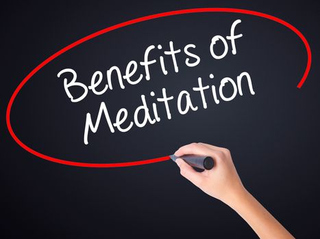 Woman Hand Writing Benefits of Meditation on blank transparent board with a marker isolated over black background. Stock Photo
