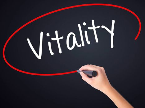 Woman Hand Writing Vitality  on blank transparent board with a marker isolated over black background. Stock Photo
