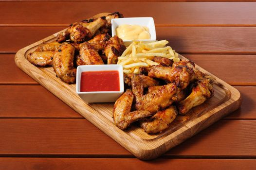 big wooden board with grilled chicken wings with french fries and two sauces, preferably served as companion for beer or other alcohol drinks