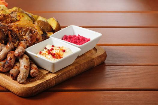 big wooden board with pork ribs and steaks baked in mustard sauce, small sausages, baked potato, grilled tomatoes and onion, hot sauce and horseraddish sauce, preferably served as companion for beer or other alcohol drinks