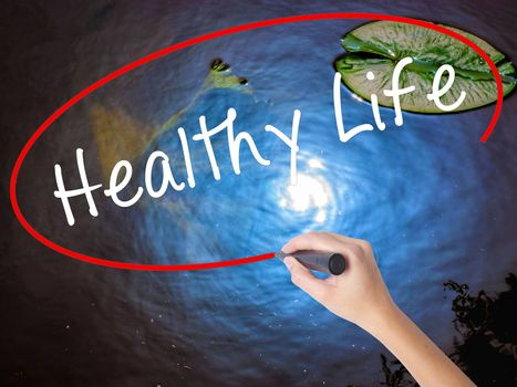 Woman Hand Writing Healthy Life marker over transparent board. Isolated on nature. Life, technology, internet concept. Stock Image