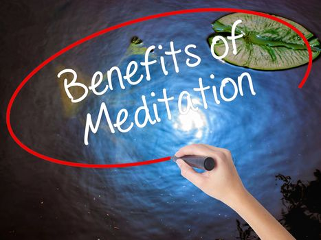 Woman Hand Writing Benefits of Meditation with marker over transparent board. Isolated on nature. Business concept. Stock Photo