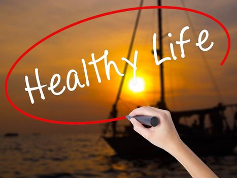 Woman Hand Writing Healthy Life black marker on visual screen. Isolated on Sunset Boat. Life, technology, internet concept. Stock Image