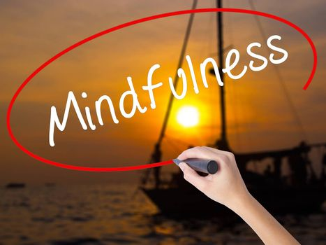 Woman Hand Writing Mindfulness  with a marker over transparent board. Isolated on Sunset Boat. Business, technology, internet concept. Stock Image