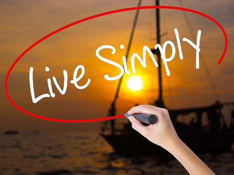 Woman Hand Writing Live Simply with a marker over transparent board. Isolated on Sunset Boat. Business concept. Stock Photo
