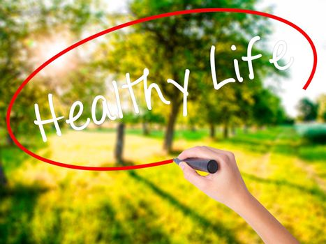 Woman Hand Writing Healthy Life black marker on visual screen. Isolated on green field. Life, technology, internet concept. Stock Image