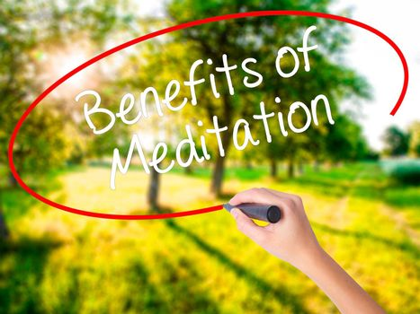 Woman Hand Writing Benefits of Meditation on blank transparent board with a marker isolated over green field background. Stock Photo