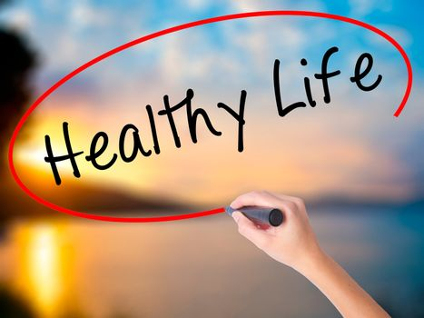 Women Hand writing Healthy Life black marker on visual screen. Isolated on Sunset. Life, technology, internet concept. Stock Image