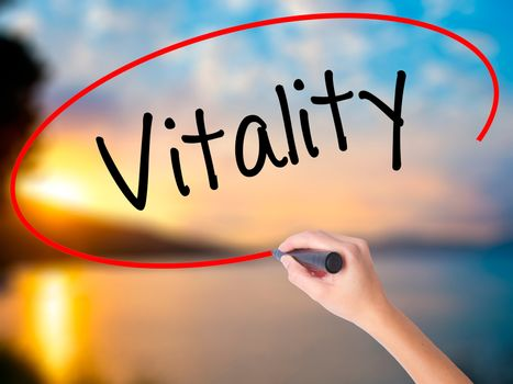 Women Hand writing Vitality  with black marker on visual screen. Isolated on Sunset. Business, technology, internet concept. Stock Photo