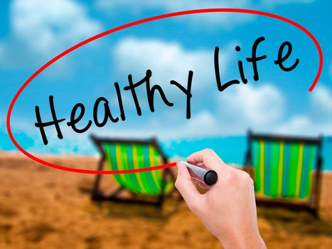 Man Hand writing Healthy Life black marker on visual screen. Isolated on sunbed on the beach. Life, technology, internet concept. Stock Image