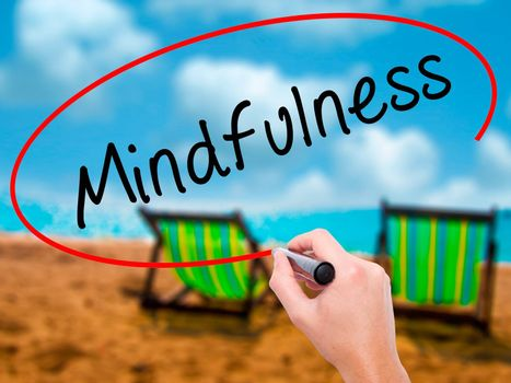 Man Hand writing Mindfulness  with black marker on visual screen. Isolated on sunbed on the beach. Business, technology, internet concept. Stock Image