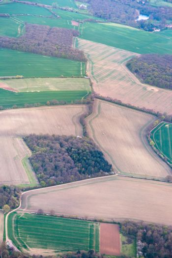 Aerial view from top on green irregular fields on south part of France. Vertical full frame crop