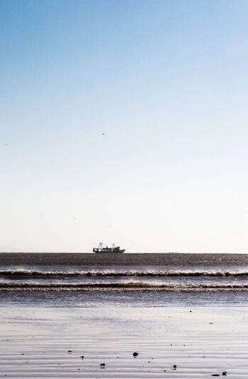 Fishing boat returning from the cruise. Low angle and long distance view. Low horizon, white space on top. Essaouira, Morocco
