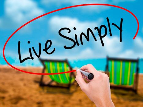 Man Hand writing Live Simply with black marker on visual screen. Isolated on sunbed on the beach. Business, technology, internet concept. Stock Photo