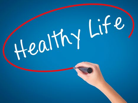 Women Hand writing Healthy Life black marker on visual screen. Isolated on blue. Life, technology, internet concept. Stock Image