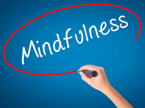 Women Hand writing Mindfulness  with black marker on visual screen. Isolated on blue. Business, technology, internet concept. Stock Image