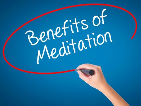Women Hand writing Benefits of Meditation with black marker on visual screen. Isolated on blue. Business, technology, internet concept. Stock Photo
