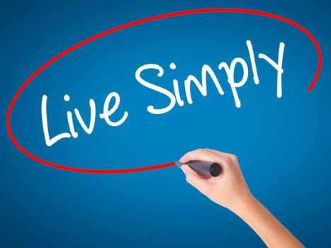 Women Hand writing Live Simply with black marker on visual screen. Isolated on blue. Business, technology, internet concept. Stock Photo