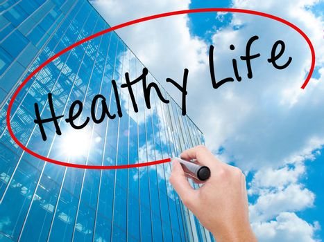 Man Hand writing Healthy Life black marker on visual screen. Life, technology, internet concept. Modern business skyscrapers background. Stock Image