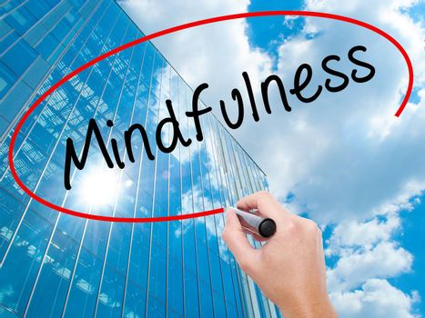 Man Hand writing Mindfulness  with black marker on visual screen. Business, technology, internet concept. Modern business skyscrapers background. Stock Image