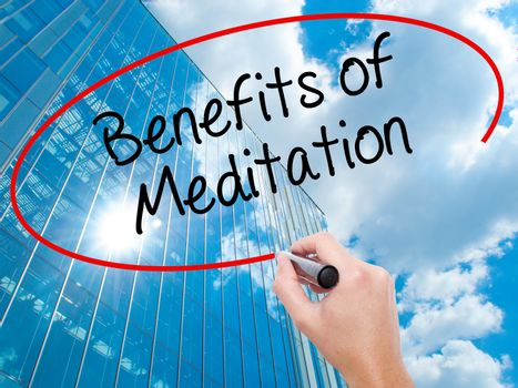 Man Hand writing Benefits of Meditation with black marker on visual screen.  Business, technology, internet concept. Modern business skyscrapers background. Stock Photo