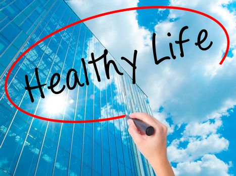 Women Hand writing Healthy Life black marker on visual screen. Isolated on skyscraper. Life, technology, internet concept. Stock Image