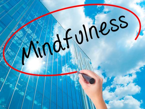 Women Hand writing Mindfulness  with black marker on visual screen. Isolated on skyscraper. Business, technology, internet concept. Stock Image