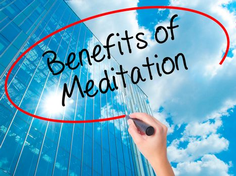 Women Hand writing Benefits of Meditation with black marker on visual screen. Isolated on skyscraper. Business, technology, internet concept. Stock Photo