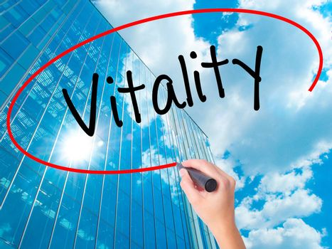 Women Hand writing Vitality  with black marker on visual screen. Isolated on skyscraper. Business, technology, internet concept. Stock Photo