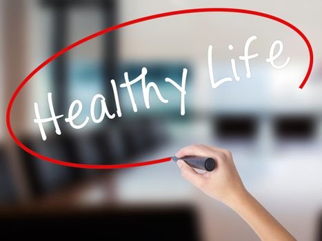 Woman Hand Writing Healthy Life black marker on visual screen. Isolated on Office. Life, technology, internet concept. Stock Image